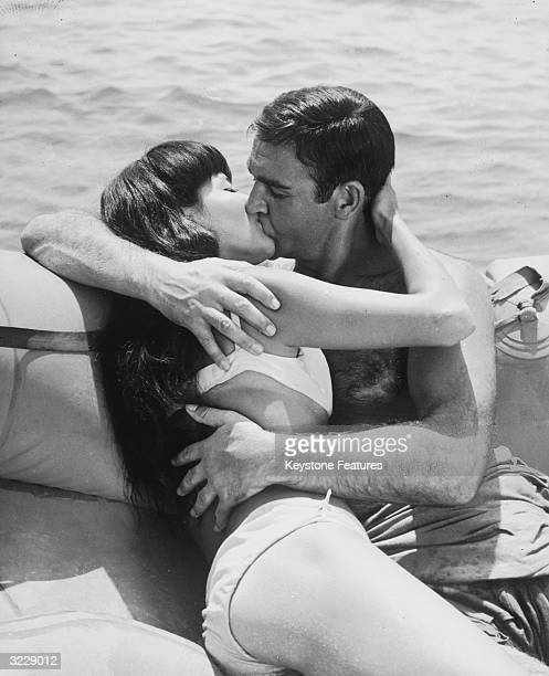 Sean Connery and Japanese actress Mie Hama locked in a passionate embrace on a boat during the filming of 'You Only Live Twice' on location in the...