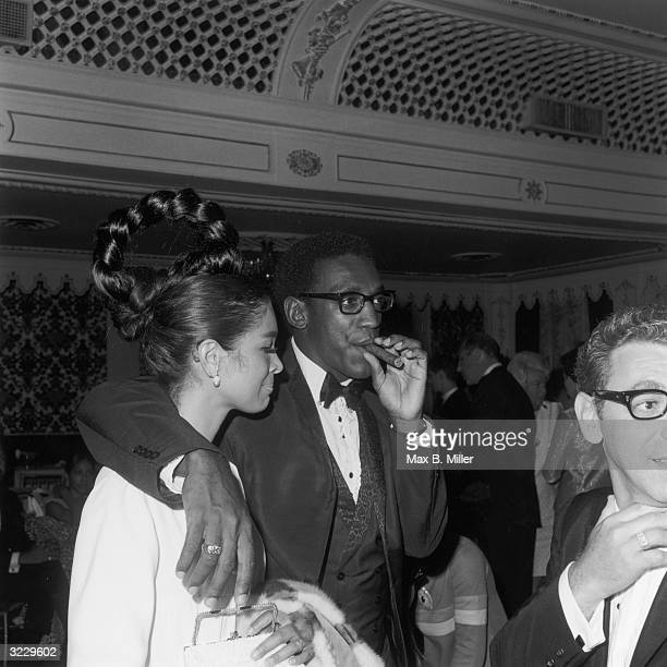 American comedian and actor Bill Cosby smokes a cigar while standing with his arm around his wife Camille Hanks at a Four Tops concert at the...