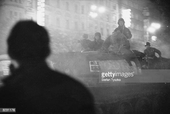 A shadowy figure watches Soviet tanks advance through the streets of Prague after nightfall