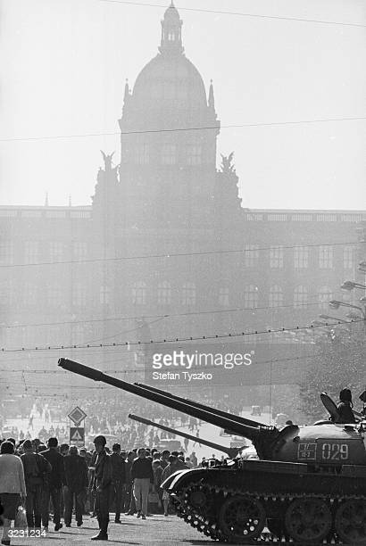 A soviet tank in St Wenceslas Square Prague in front of crowds of protesters and the shadowy silhouette of Prague's National Museum