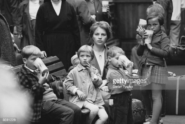 A young family leaving to escape the Soviet invasion await transport to the West at Prague's central railway station