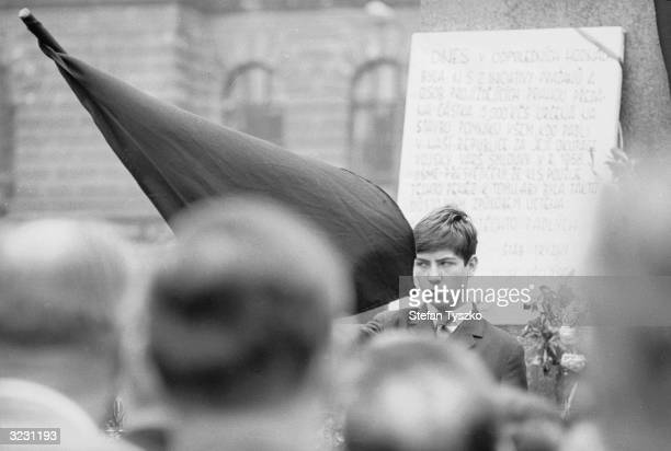 A young student stands black flag in hand at the foot of the statue of St Wenceslas as a crowd gather to listen to speakers The statue situated in...