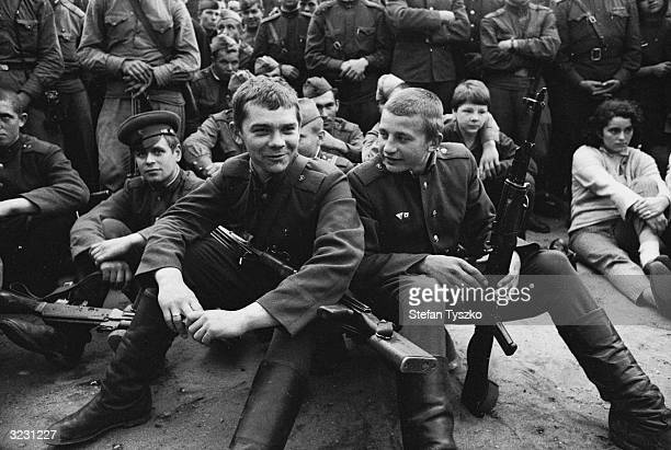 Armed Soviet troops watch the entertainment provided by the Red Army Ensemble at their encampment in a Prague park during their country's invasion of...
