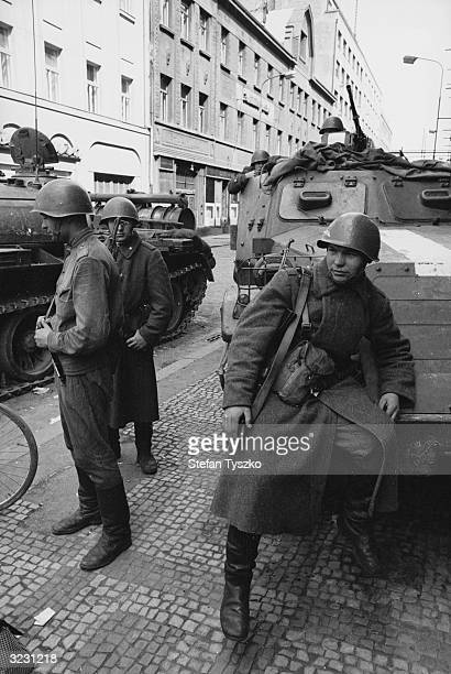 Soviet troops on the streets of Prague man a blockade of tanks and armoured personnel carriers
