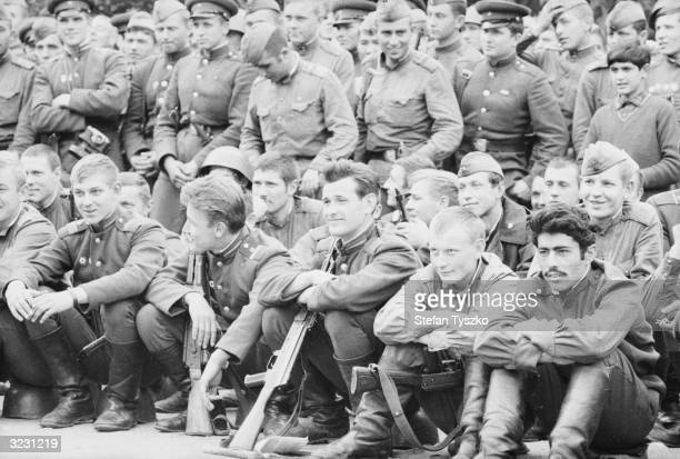 Soviet troops watch the entertainment provided by the Red Army Ensemble at their encampment in a Prague park during their country's invasion of...