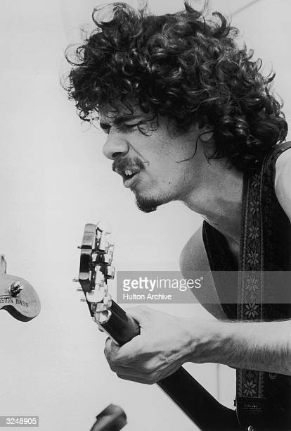 Mexicanborn American guitarist and bandleader Carlos Santana plays guitar on stage during his band's performance at the Woodstock Festival Bethel New...