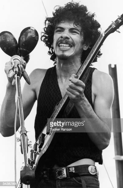 Mexicanborn American guitarist and bandleader Carlos Santana holds maracas and an electric guitar while performing at the Woodstock Music Festival in...