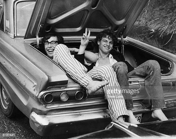 Two young men in the boot of a car after hitching a lift home from the Woodstock Music and Arts Fair