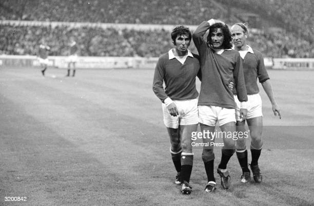 An unbelieving George Best the Manchester United and Irish International is helped off the field by teammates Bobby Charlton and Tony Dunne during a...