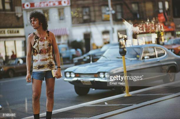 A patterned vest cutoff jeans and a wild perm are the street wear for this New Yorker