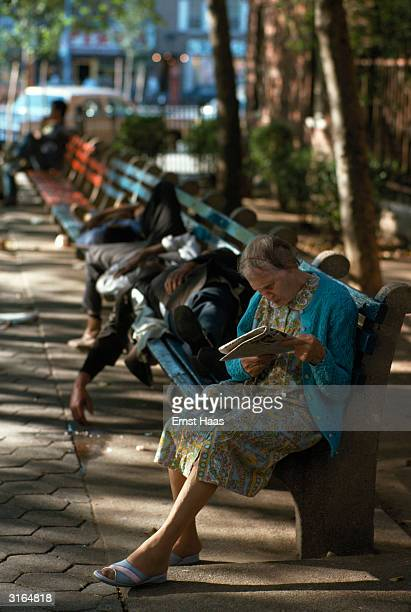An elderly woman sits on a bench reading in a shady city square while beside her downandouts sprawl asleep
