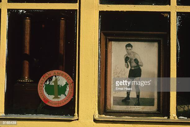 Yellow painted window of the 'Italian American Civil Rights League' displaying their logo on one side and on the other a photograph of boxer Tony...