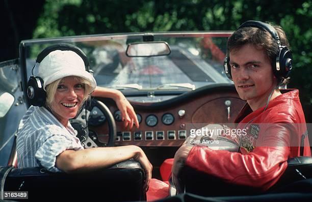 Wearing headphones Countess Gunilla Bismarck driving a sports car in Marbella her passenger is racing driver Count John F Ledebur