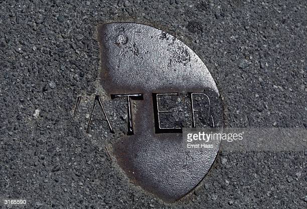 A metal plaque inscribed with the word 'Water' half hidden under concrete in Maine