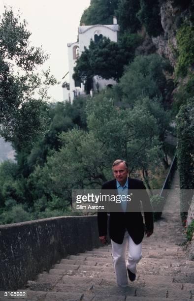 Writer Gore Vidal climbing hillside steps at Ravello in Italy