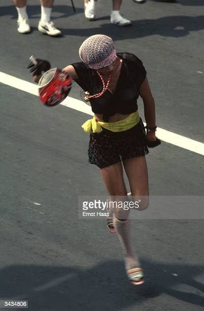 A participant in a festival in Aomori in a miniskirt carrying a fan and wearing a net mobcap