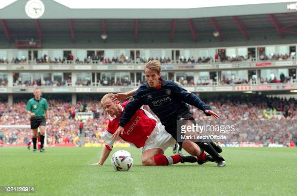 22 August 1999 Premiership Football Arsenal v Manchester United Dennis Bergkamp of Arsenal goes down under a challenge from Phil Neville of...