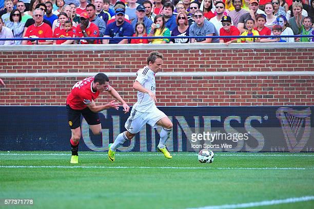 Real Madrid midfielder Luka Modric runs away from Manchester United defender Michael Keane during the Real Madrid v Manchester United match Saturday...