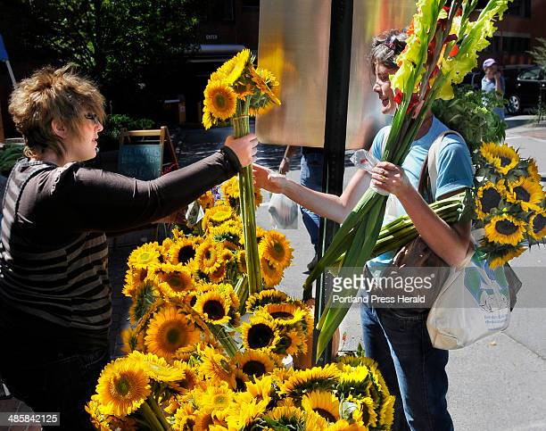 PHOTOGRAPHER August 20 2008 It was a beautiful sunny day as Stephanie Abrams of South Portland right purchases a copule of bunches of sunflowers from...