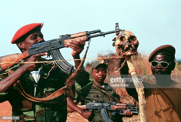 Soldiers stretch a piece of rope tied to a skull across the road to mark the roadblock at the Angolan military encampment near the river Kwanza...