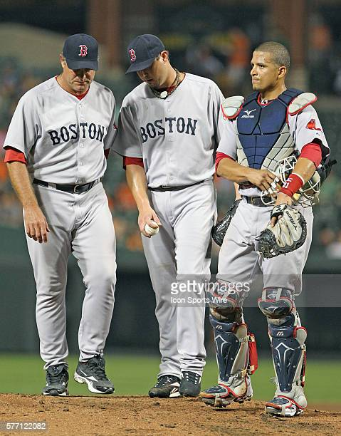 Red Sox pitcher Josh Beckett talks with pitching coach John Farrell and catcher Victor Martinez in action during the Baltimore Orioles 5-2 victory...