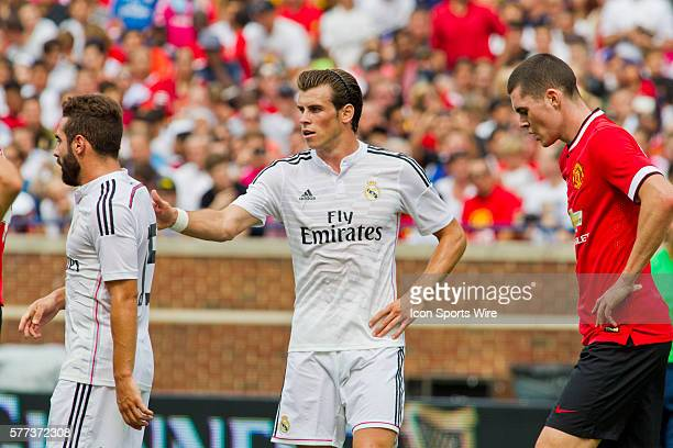 Real Madrid forward Gareth Bale center reaches out to defender Daniel Carvajal left as Manchester United defender Michael Keane right walks by during...