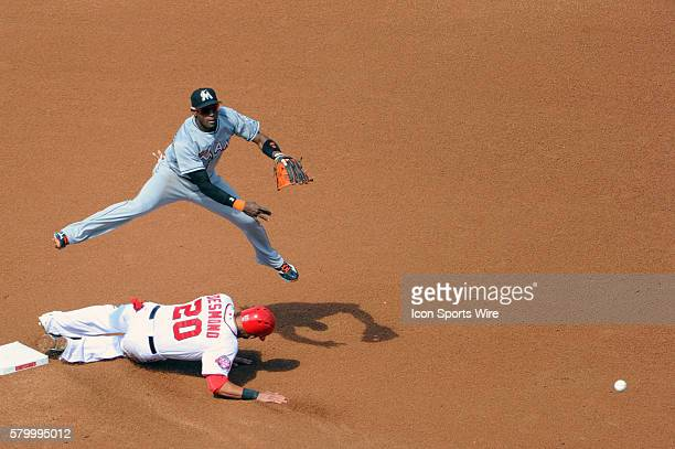 Miami Marlins shortstop Adeiny Hechavarria completes a double play against Washington Nationals shortstop Ian Desmond at Nationals Park in...