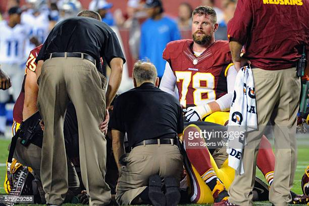 Washington Redskins center Kory Lichtensteiger looks on as quarterback Robert Griffin III is attended to after being injured at FedEx Field in...