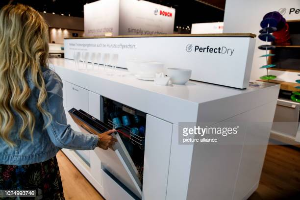 August 2018, Berlin, Germany: A woman at the electronics trade fair IFA is looking at a dishwasher at the stand of the manufacturer Bosch. The...