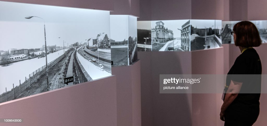 A Woman Stands In The Alte Münze In Front Of Historical Photos