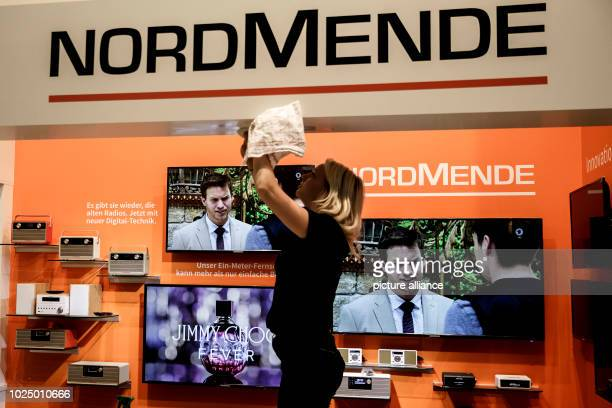 """August 2018, Germany, Berlin: A cleaner is cleaning Nordmende's digital radio stand at the IFA electronics trade fair. The """"Consumer Electronics..."""