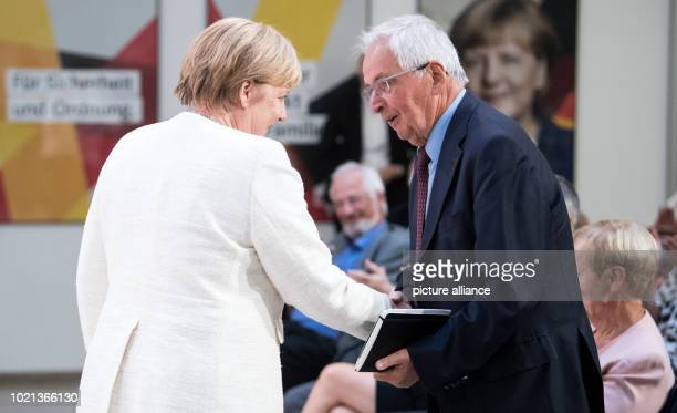 Former German Environment Minister Klaus Toepfer thanks Angela Merkel German Chancellor and Chairwoman of the Christian Democratic Union for her...