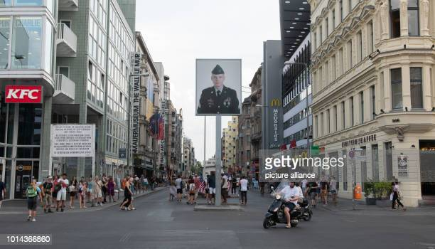 Numerous people are on the road at Checkpoint Charlie during the day At the former border crossing point for diplomats in Berlin American and Soviet...