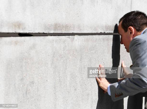 US Ambassador to Germany Richard Grenell looks through a gap between the wall parts at the Berlin Wall Memorial on Bernauer Strasse The construction...