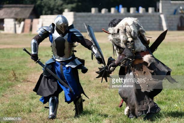 Two participants of the fantasy live roleplaying game 'ConQuest of Mythodea' fight as warriors of the 'Black Ice' and as 'Orc' on the fictitious...