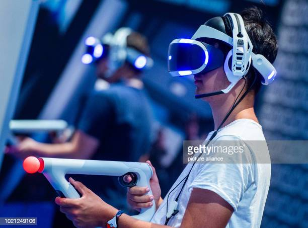 A visitor to Gamescom 2018 tries out a video game with VR glasses at a stand For the tenth time the Computer Spielemesse takes place in Cologne Photo...