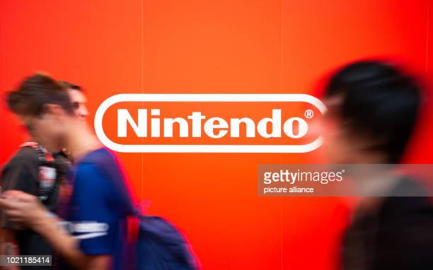 August 2018, Germany, Cologne: Visitors to Gamescom pass the Nintendo logo. For the tenth time the Computer Spielemesse takes place in Cologne....