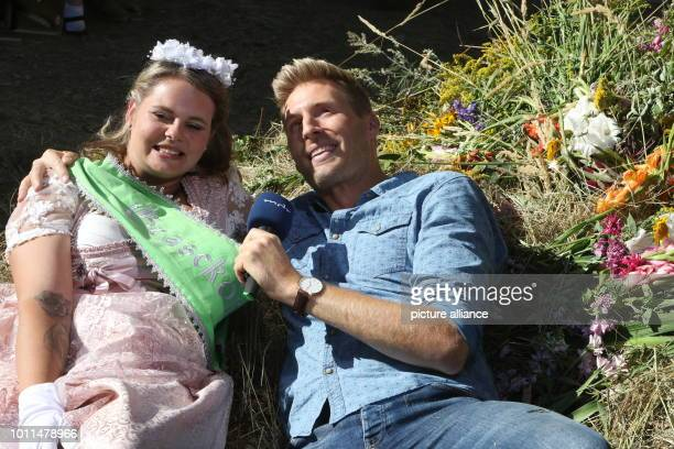 """August 2018, Germany, Huettenrode: Presenter Maximilian Arland and """"Grasekoenigin"""" Sina Meinhardt lie in the hay. He shot the TV format """"Musik auf..."""