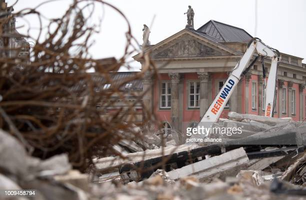 Against the backdrop of renovated old buildings a digger works on the final demolition of a former building of the Fachhochschule Potsdam vocational...