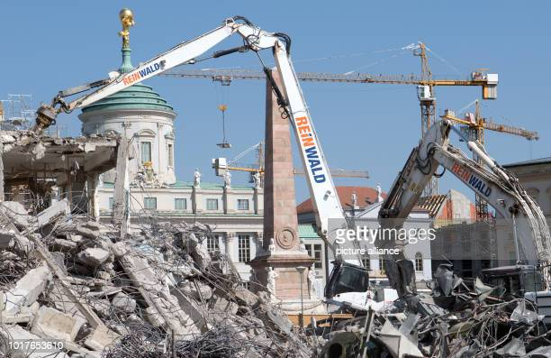 Excavators demolish the last remains of the building of the old University of Applied Sciences against the backdrop of the Old Town Hall Construction...