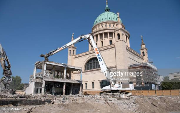 Excavators demolish the last remains of the building of the old University of Applied Sciences against the backdrop of the Nikolaikirche Construction...