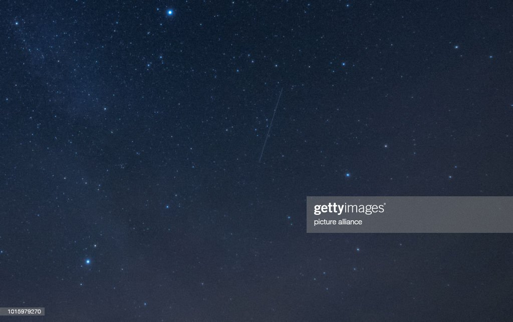 Stars and a shooting star can be seen in the sky not far