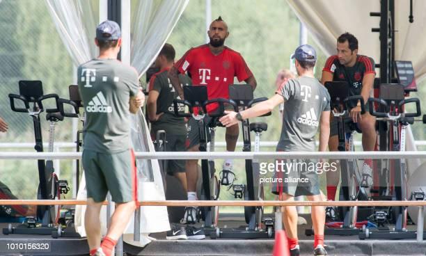 August 2018, Germany, Rottach-Egern: Arturo Vidal and sports director Hasan Salihamidzic from FC Bayern Munich sitting on ergometers. The club is...