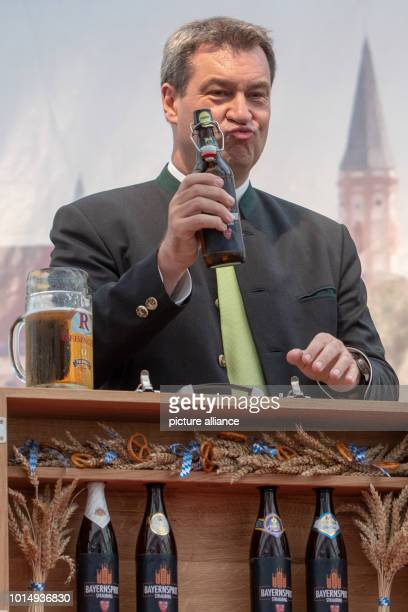 August 2018, Germany, Straubing: Markus Soeder of the Christian Social Union , Premier of Bavaria, holds a beer bottle in his hand after his speech...