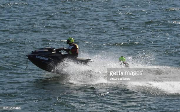 August 2018, Germany, Zinnowitz: Marcel Seminsti, the lifeguard of the DRK water rescue service, practices the water rescue on the rescue board...