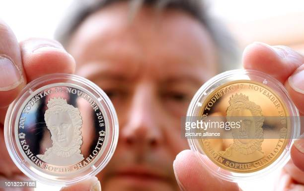 The strictly limited commemorative coins in gold and silver on the 200th anniversary of the death of Queen Sophie Charlotte are shown by Michael...