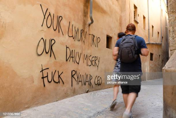 Passersby walk past a historic house in the city centre The wall of the hourse reads 'Your luxury trip our daily misery fuck Ryanair CEO' Photo Clara...
