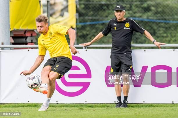 August 2018, Switzerland, Bad Ragaz: Soccer, training camp Borussia Dortmund: Dortmund's Lukasz Piszczek plays a pass in front of Dortmund's coach...