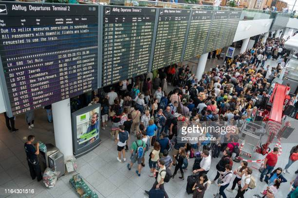 Passengers are standing in Terminal 2 of Munich Airport under a scoreboard on which many flights are indicated as cancelled waiting for the reopening...