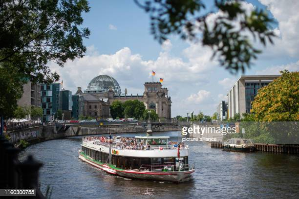 August 2019, Berlin: An excursion ship crosses the Spree river in summer weather in front of the Reichstag. Photo: Arne Immanuel Bänsch/dpa